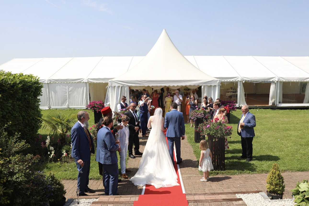 Newlyweds and guests outside marquee