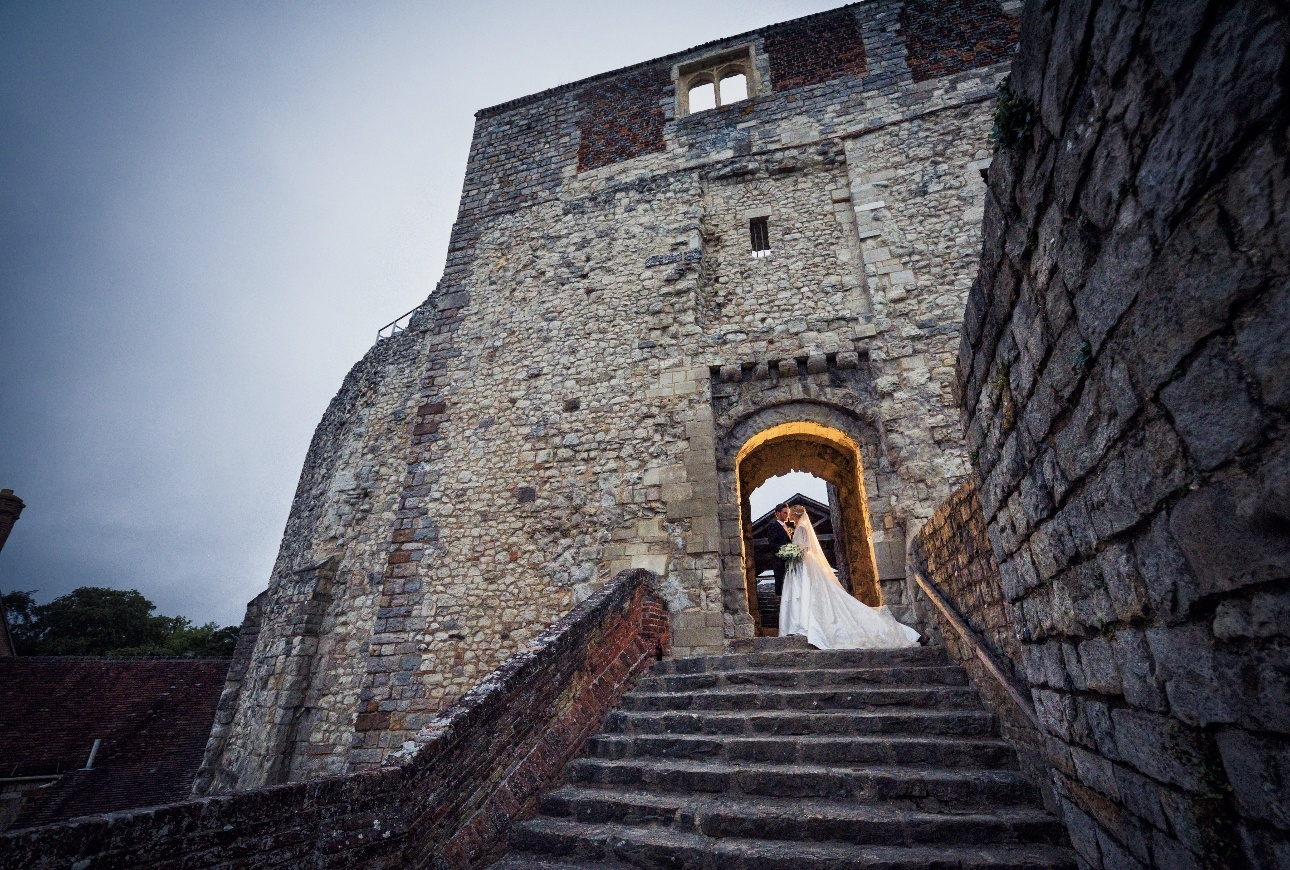 Couple pose on steps in castle