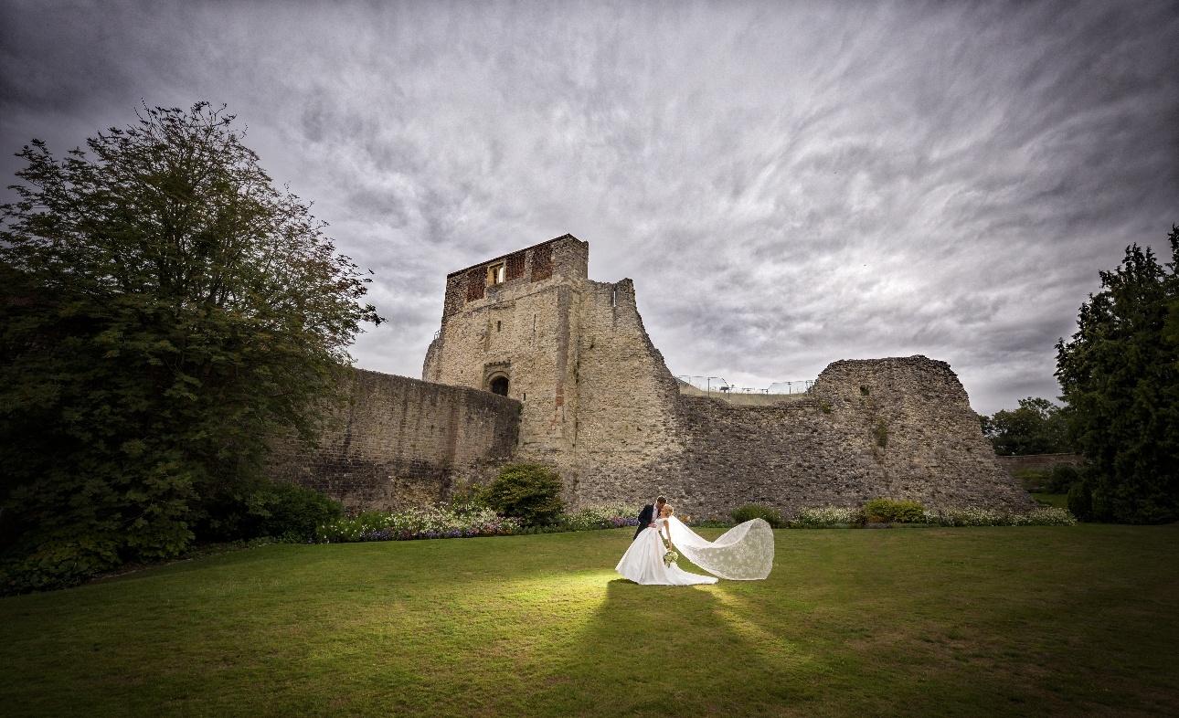 Brides veil flowing in castle gorunds