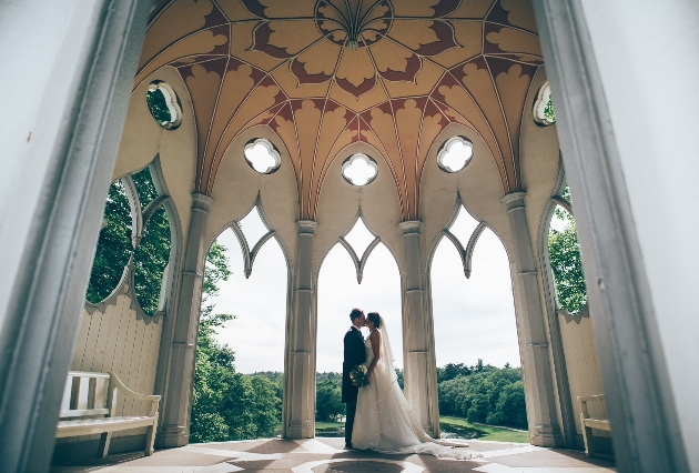 Couple kiss under the white Gothic temple at Painshill in Surrey featured in Bridgerton